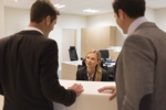 Businessmen communicating with female receptionist